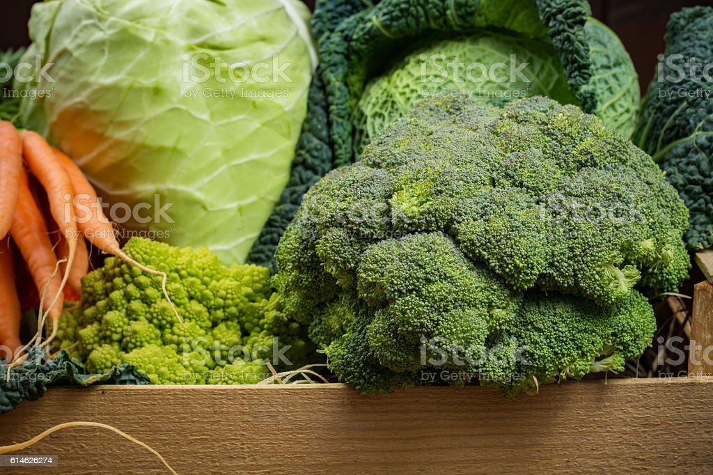 Green and orange fresh vegetables in wooden box, harvest stock photo