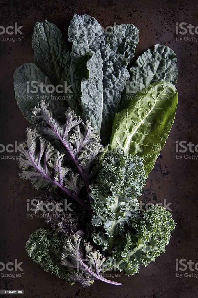 Green and purple kale leaves on rustic background stock photo