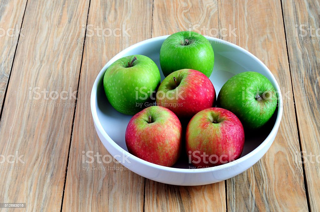 Green and red apple on a bowl stock photo