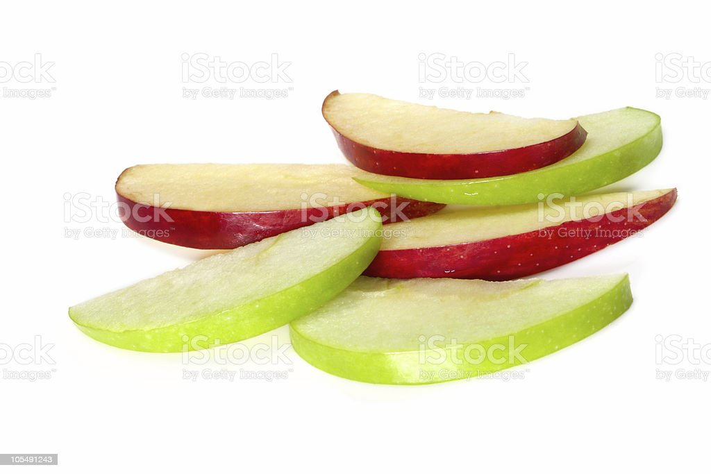 Green and red apple slices stacked on white background stock photo