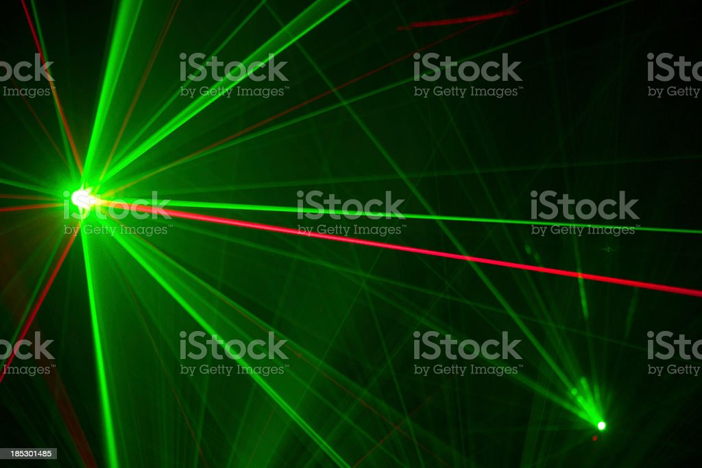 Green and red laser trails light up the darkness stock photo