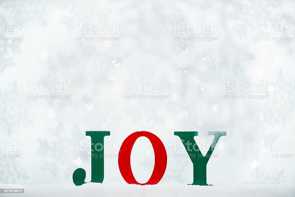 Green and Red word JOY in the snow with bokeh stock photo
