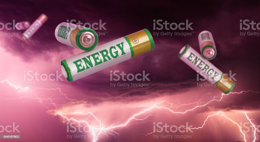 Green and renewable energy concept. Green and golden colored batteries flying in the air on a thunderstorm and lighting background stock photo