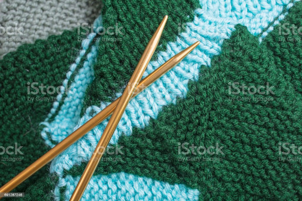 Green and teal knitted socks with gold metal needles stock photo