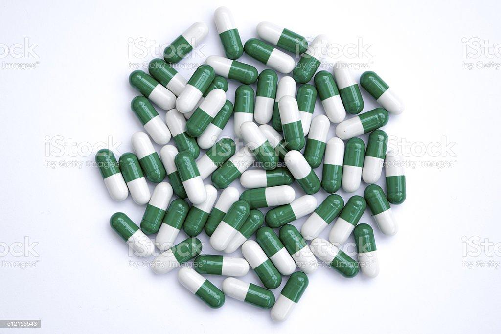 Green and white pills stock photo
