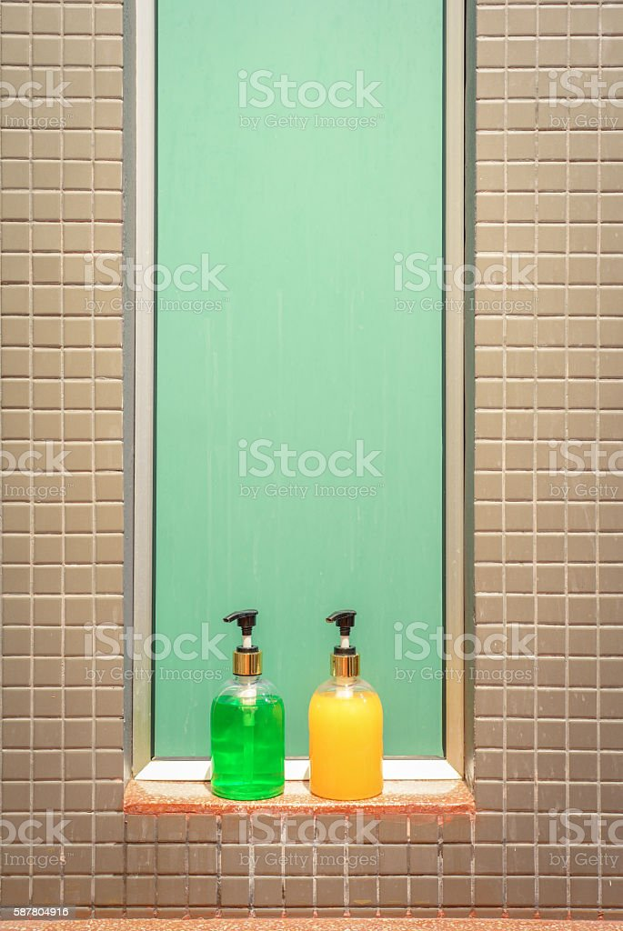 Green and yellow bottles of soap shampoo against tiled wall photo libre de droits