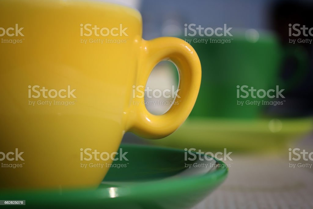 Green and yellow cup of coffee stock photo