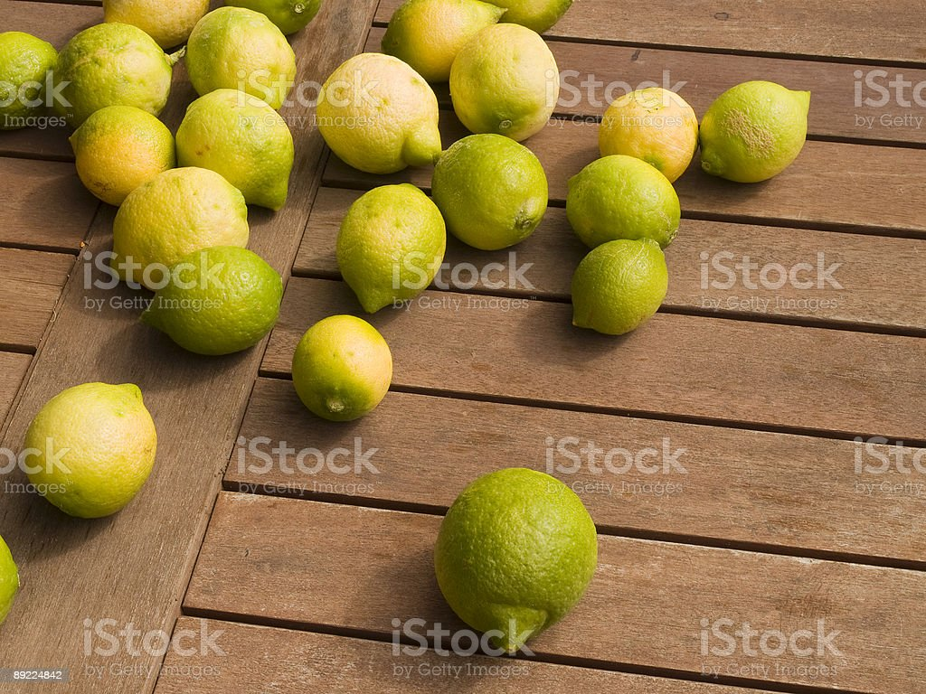 Green and yellow lemons on a wooden table royalty-free stock photo