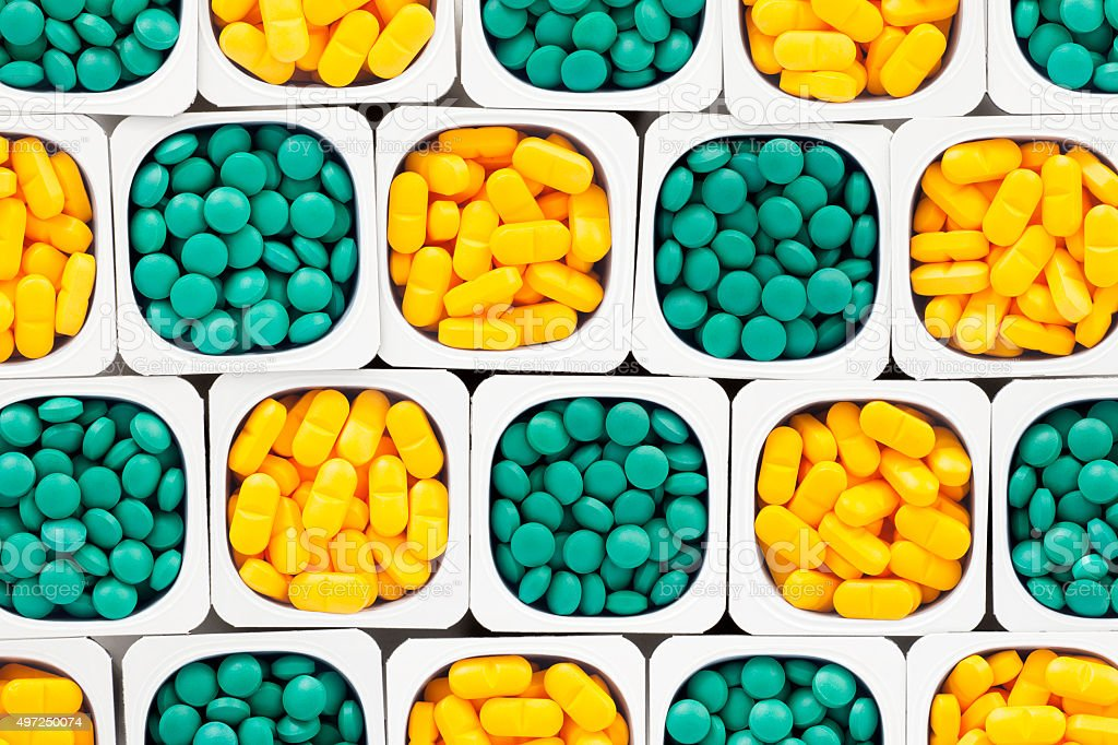 Green and yellow pills stock photo