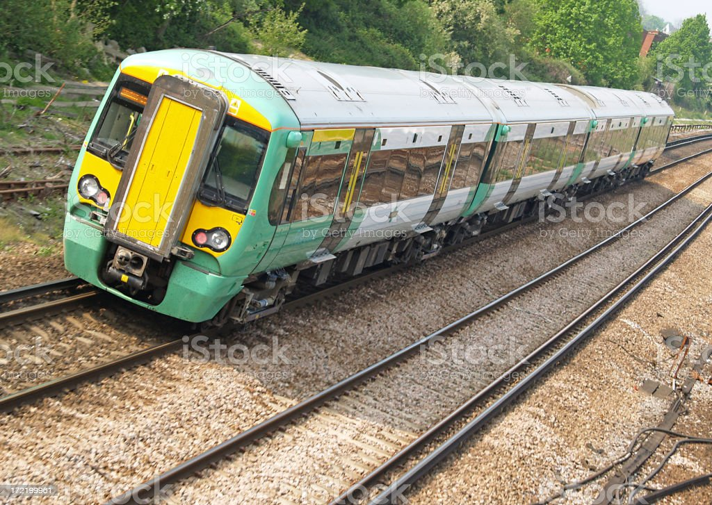 Green and yellow subway train traveling on the tracks  royalty-free stock photo
