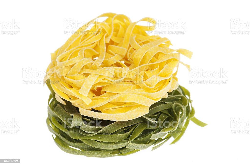 Green and yellow tagliatelle on white royalty-free stock photo