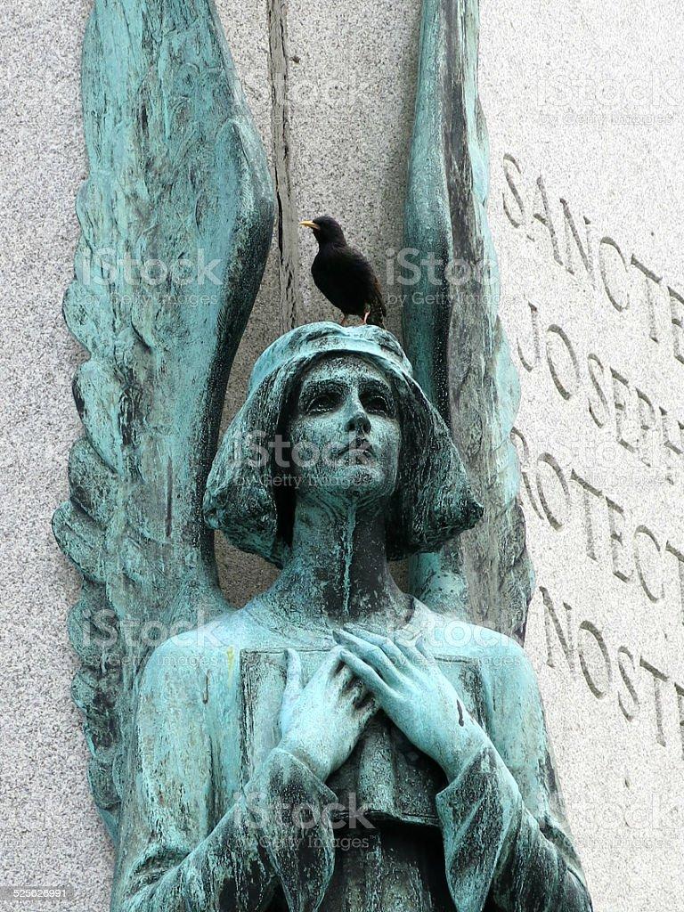 Green Angel Statue with Black Bird on Head stock photo
