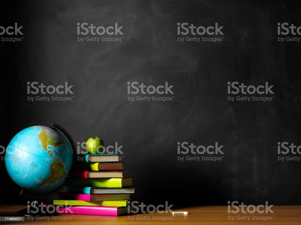 Green Apple and Books on a Classroom Desk with Globe stock photo