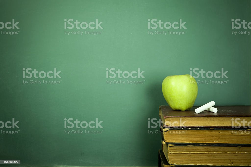 Green apple and chalk sitting on education books royalty-free stock photo