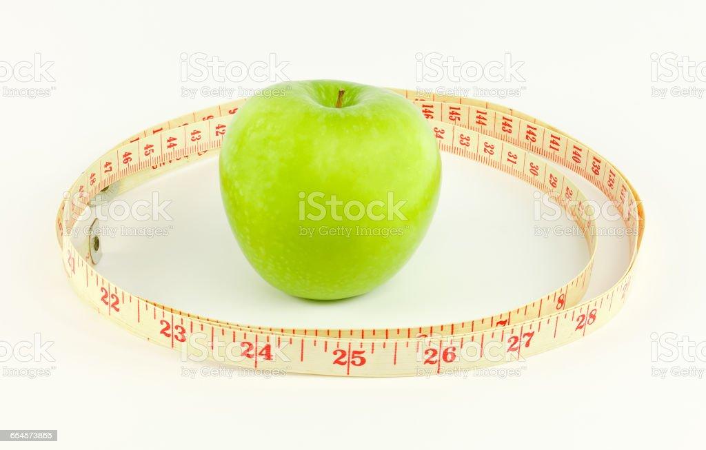 Green apple and measure waist. stock photo