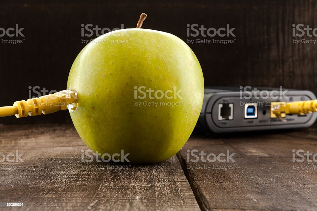 Green apple connected to a data network and a router stock photo
