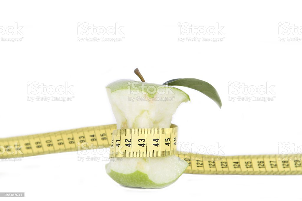 Green apple core and measuring tape. Diet concept stock photo
