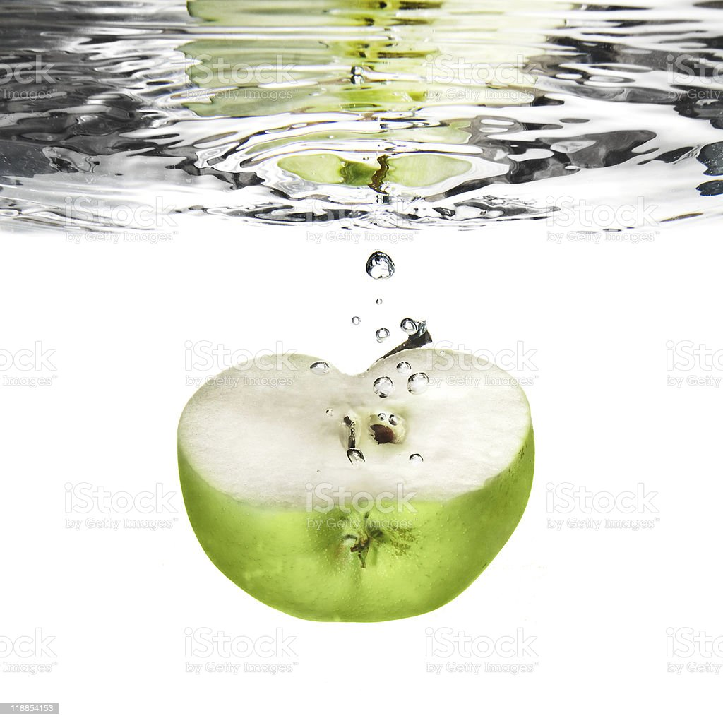 green apple dropped into water with bubbles isolated on white royalty-free stock photo