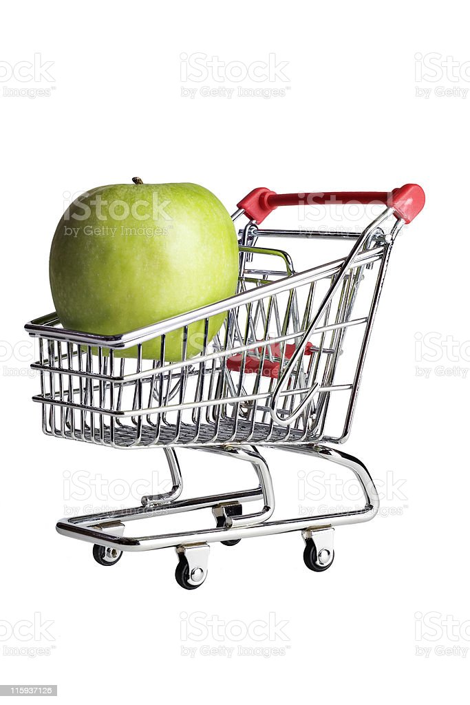 Green apple in a miniature shopping cart. royalty-free stock photo