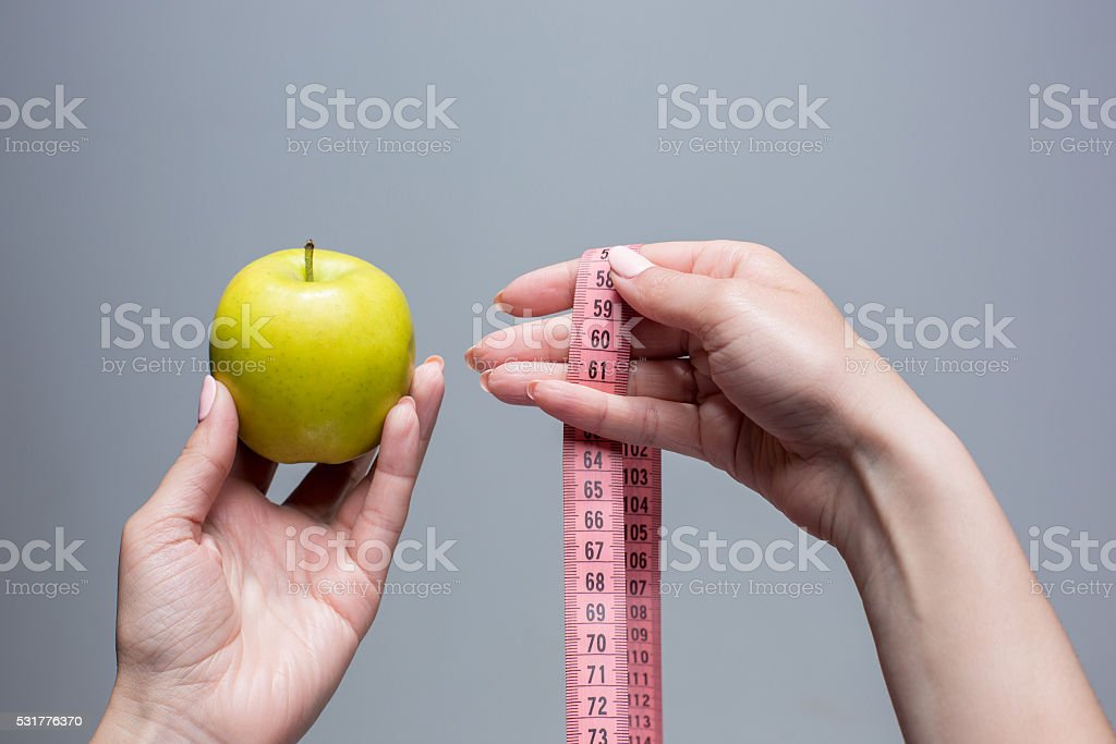 Green apple in female hands on gray background. Weight loss stock photo
