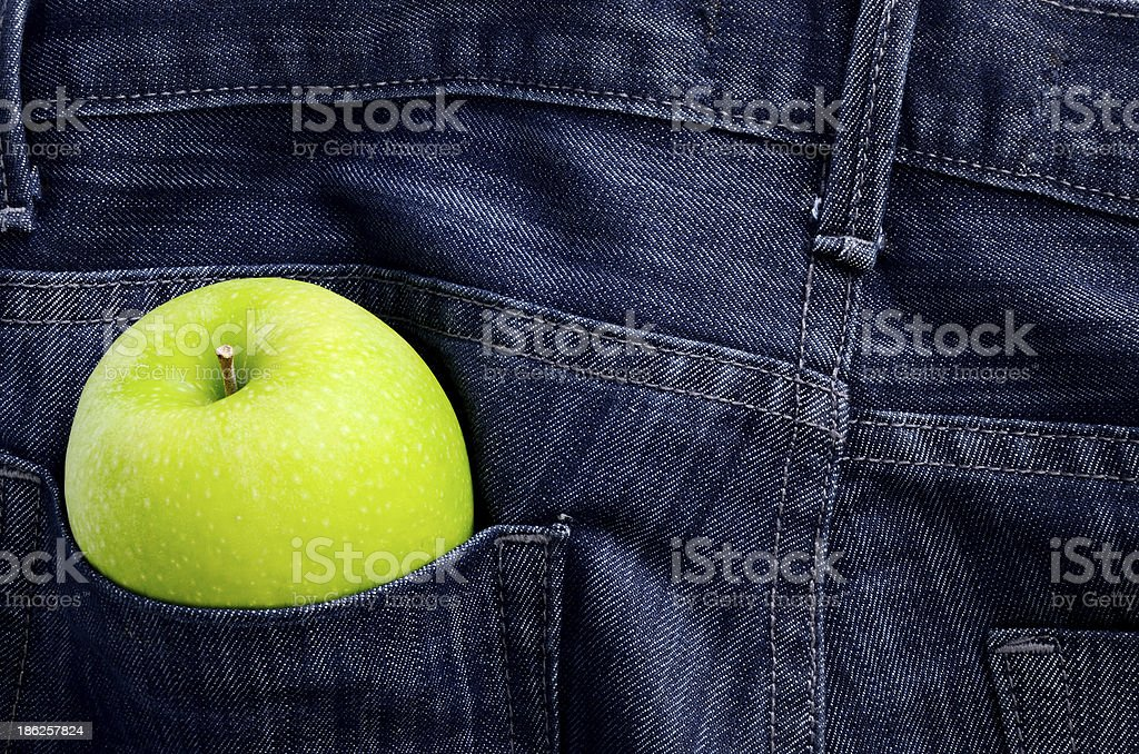 Green apple in Jeans pocket royalty-free stock photo