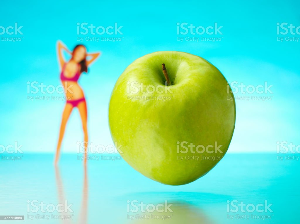 Green Apple in the Air with a Bikini Clad female stock photo