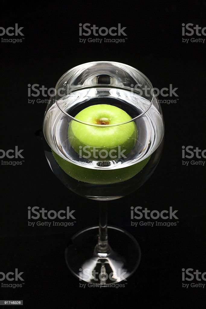 Green apple in wine glass stock photo