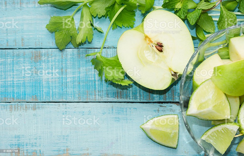 Green apple, lime cut and celery on blue wood stock photo