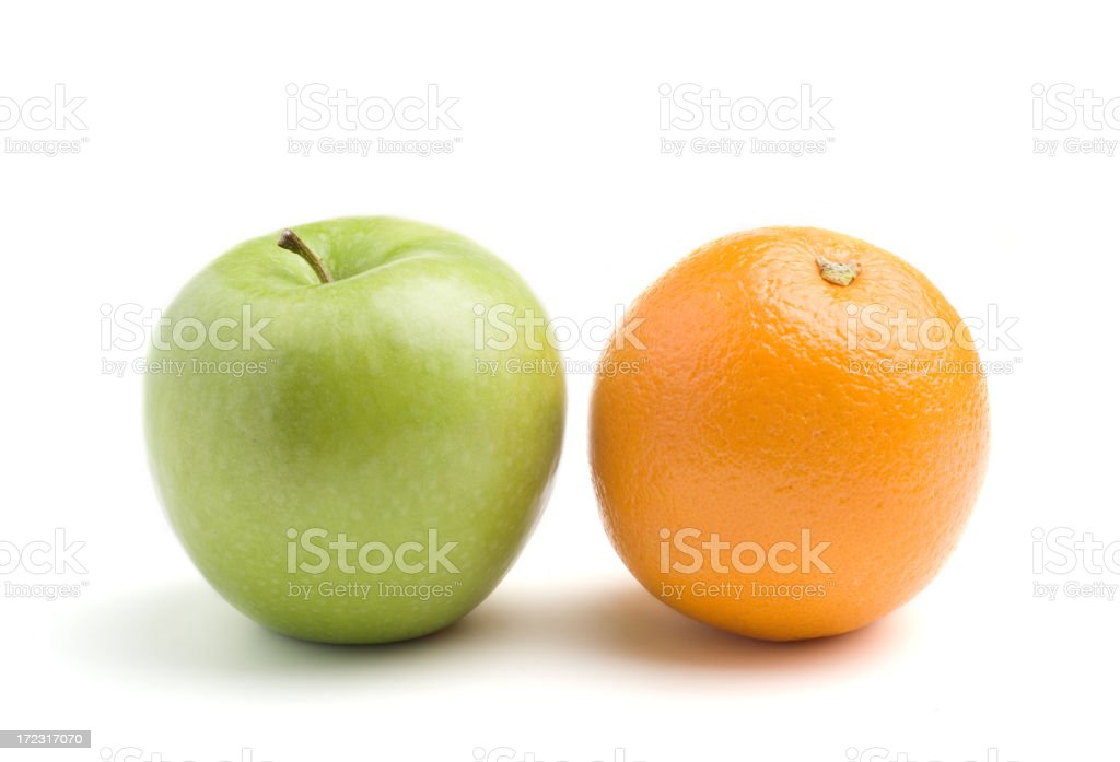 A green apple next to an orange, isolated on white stock photo