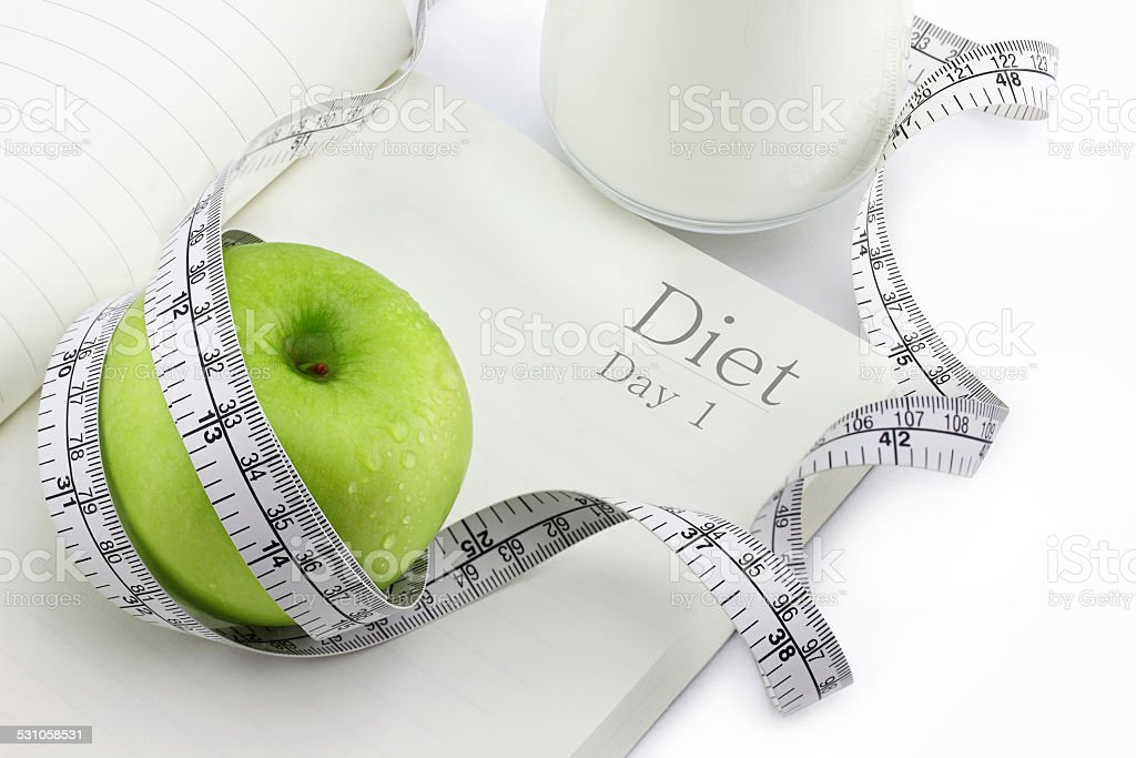 Green apple on a notebook and measuring tape, Diet concept. stock photo