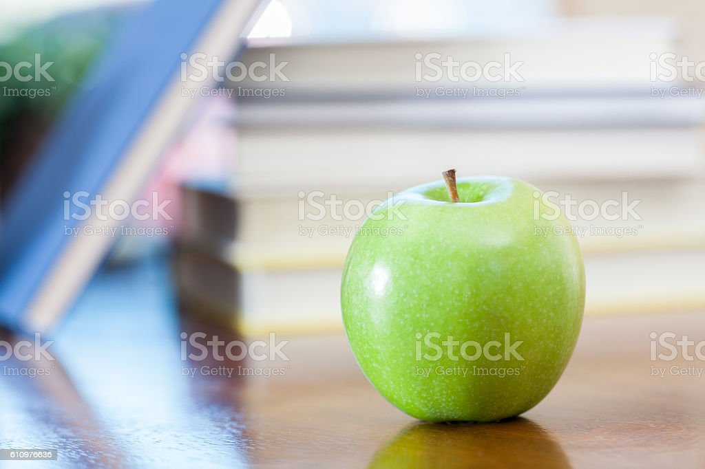 Green apple on desk in front of stack of books stock photo