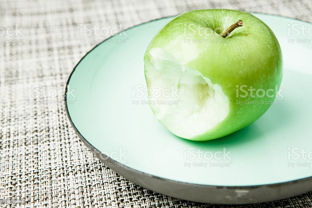 Green apple on plate, missing bite stock photo