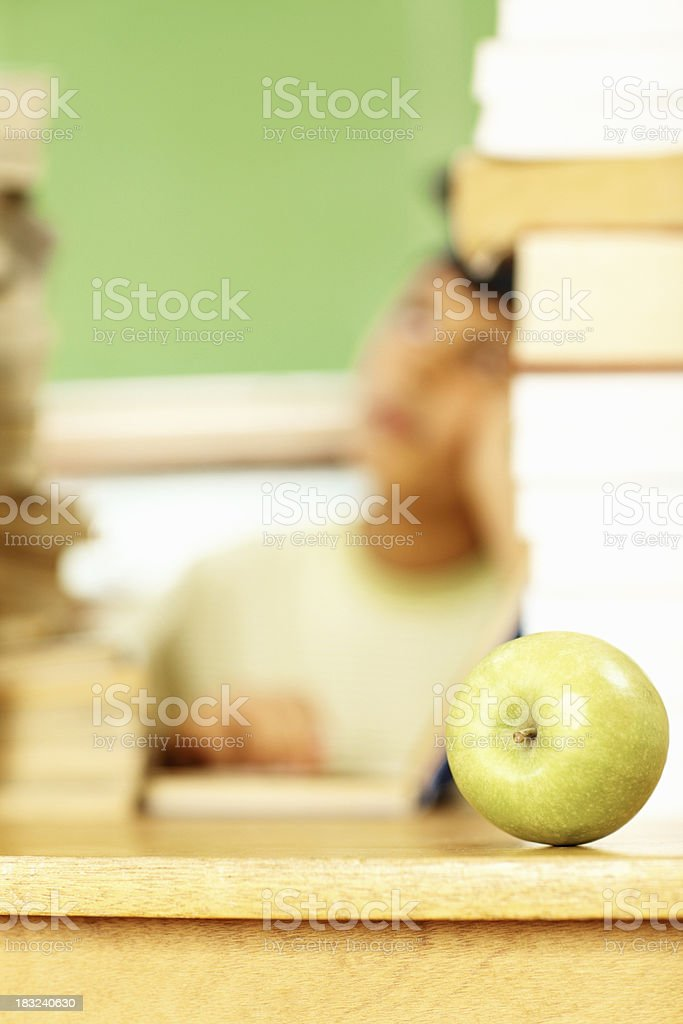 Green apple placed on a desk, boy in the background royalty-free stock photo