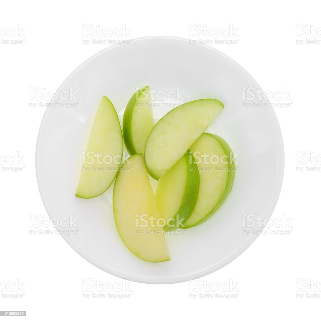 Green apple slices on a plate top view stock photo