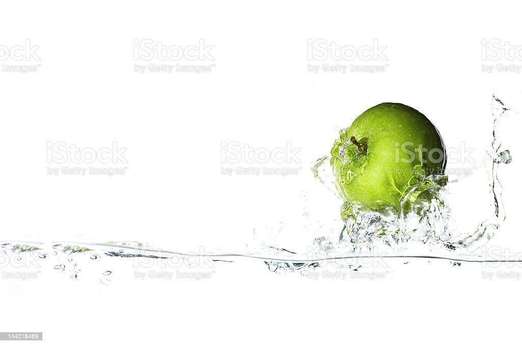 A green apple splashing in clear water royalty-free stock photo
