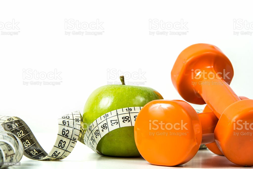 Green apple, tape measure and dumbbells stock photo