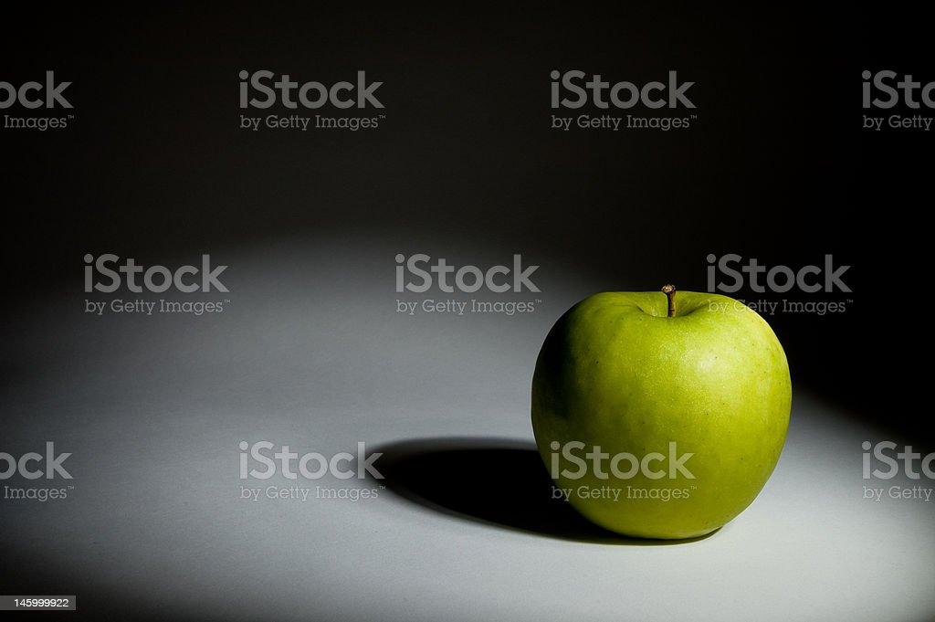 Green apple under the spot stock photo
