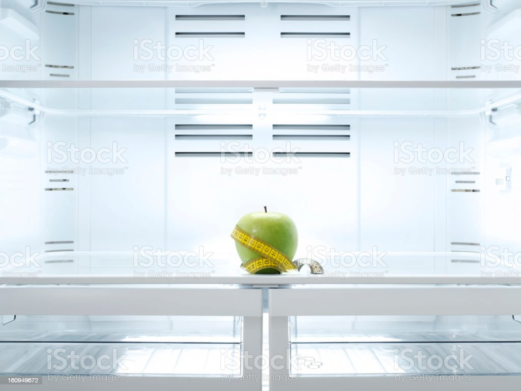 green apple with a measuring tape around it royalty-free stock photo
