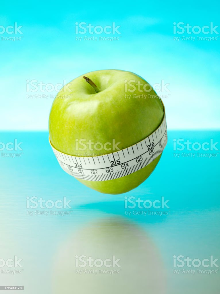 Green Apple with a Tape Measure Around it's Middle stock photo