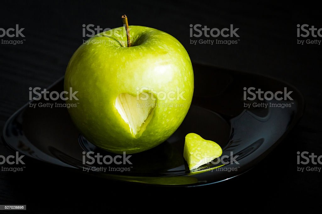 green apple with carved heart stock photo