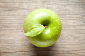 Green apple with leaf on old wooden table