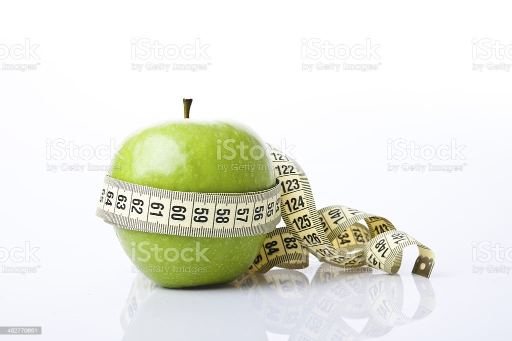 Green apple with measuring tape around it. stock photo