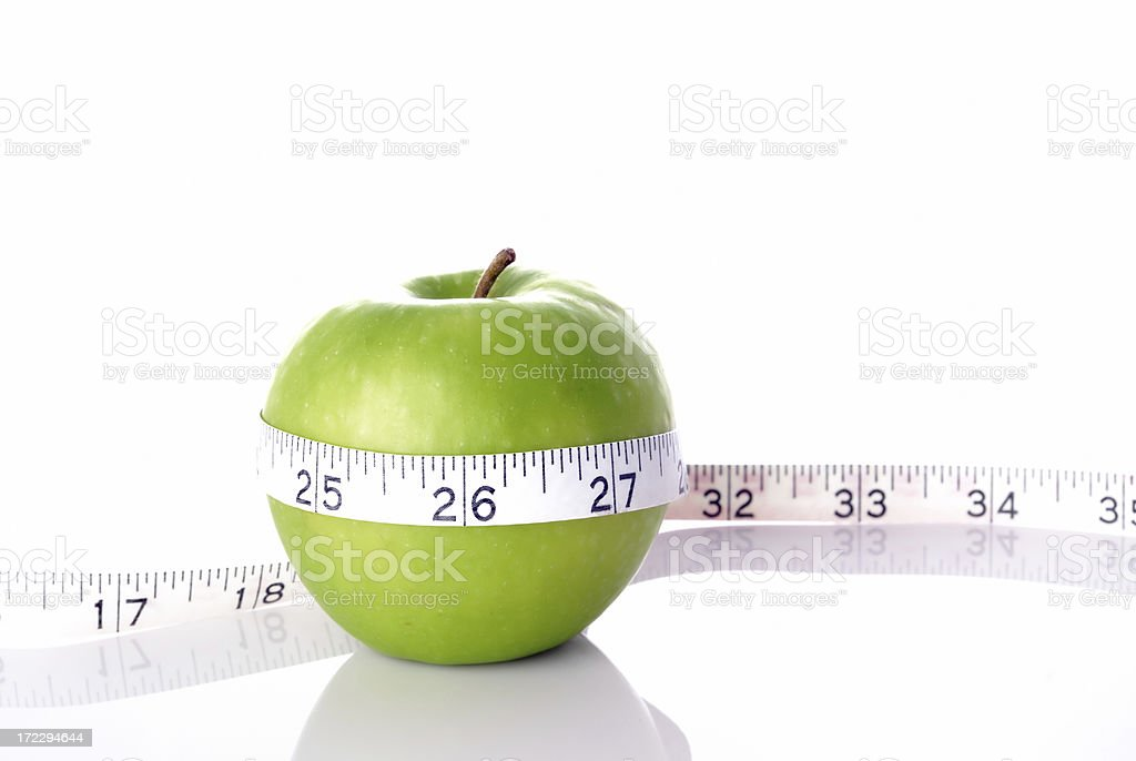 Green apple with measuring tape royalty-free stock photo