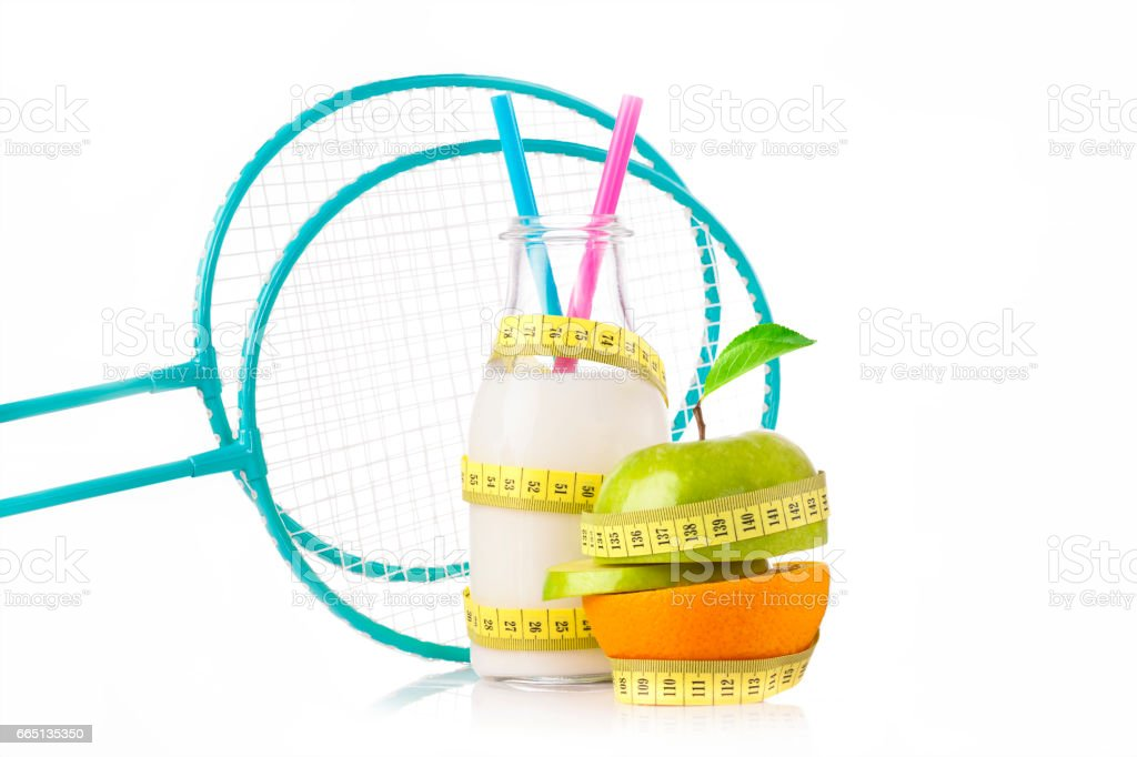 Green apple with measuring tape with a pair of blue fitness dumbbells and protein drink stock photo
