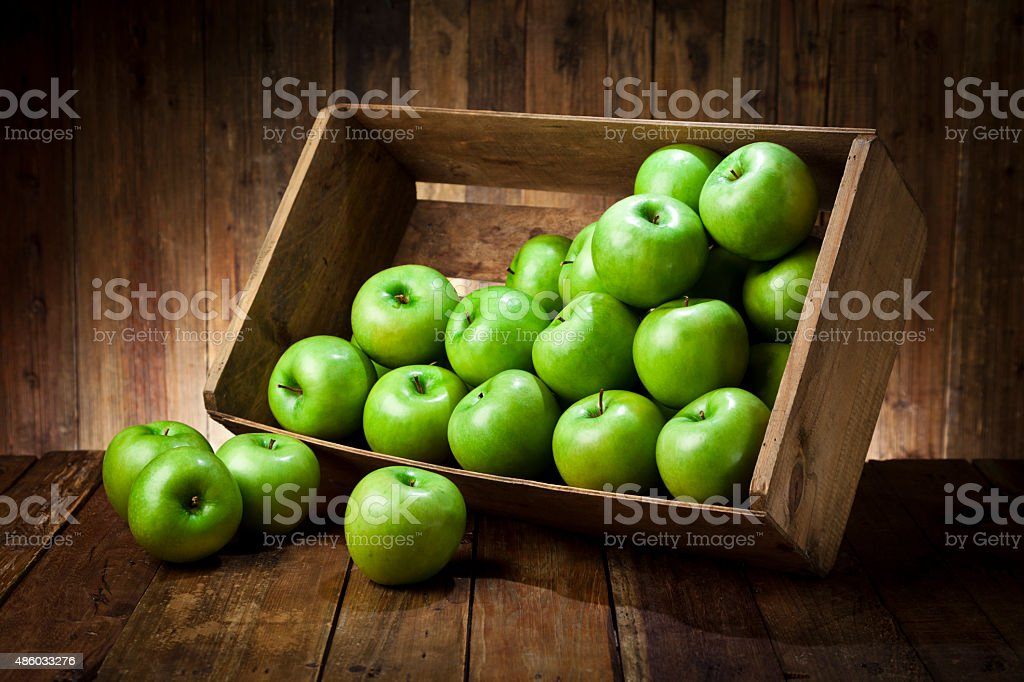 Green apples in a crate on rustic wood table stock photo