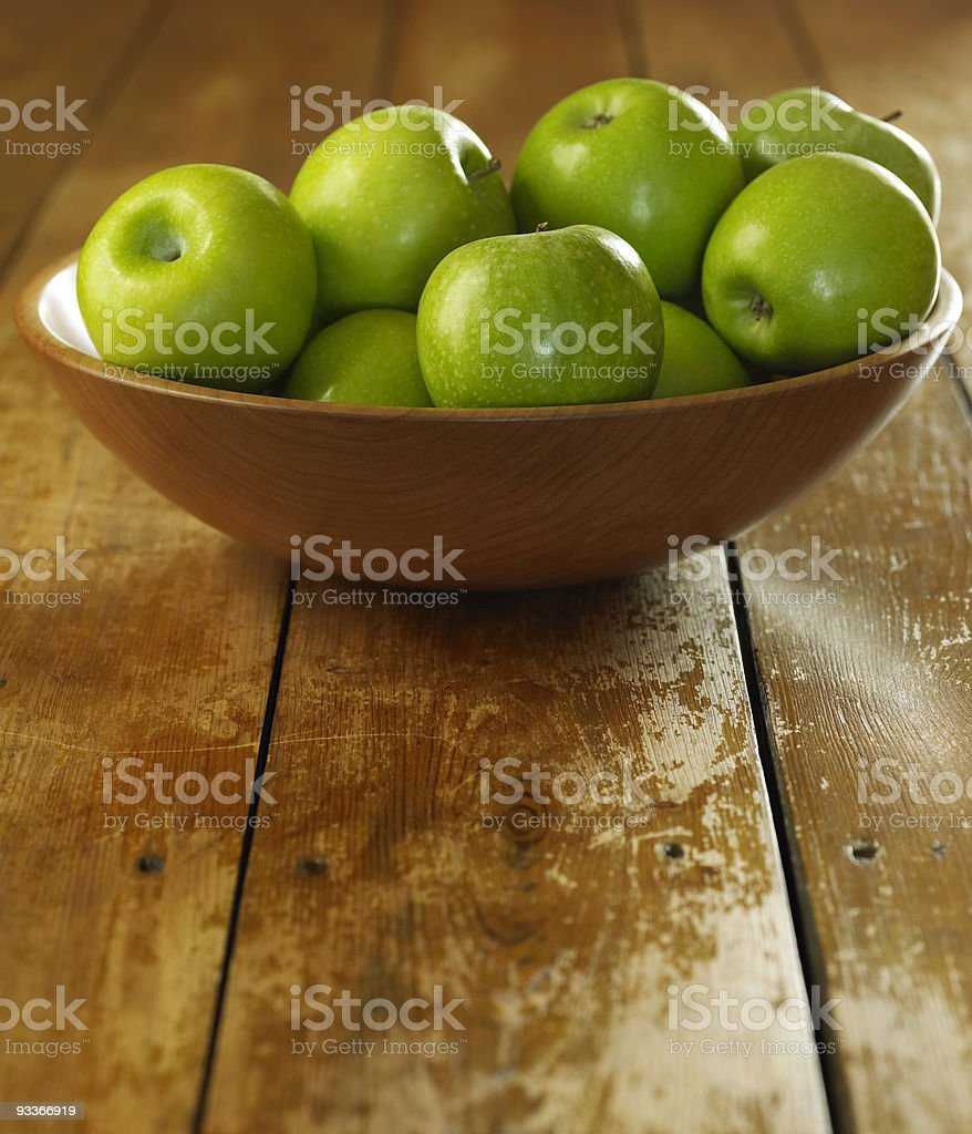 Green apples in wooden bowl on wooden floorboards stock photo