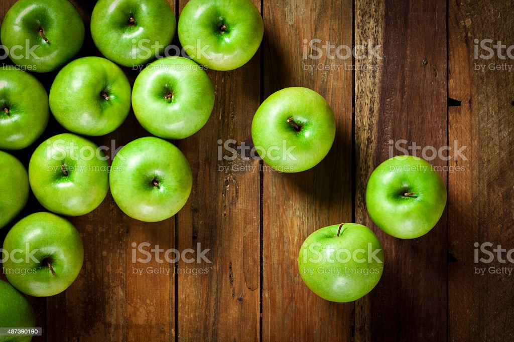Green apples on rustic wood table shot directly above stock photo