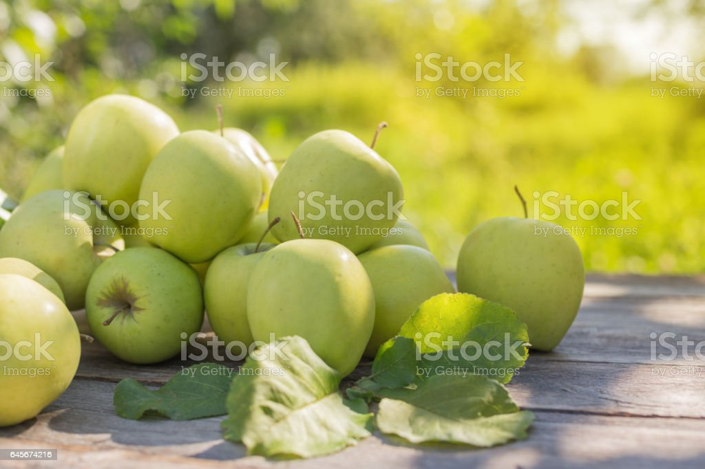 green apples on wooden background outdoor stock photo