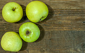 Green apples on wooden background