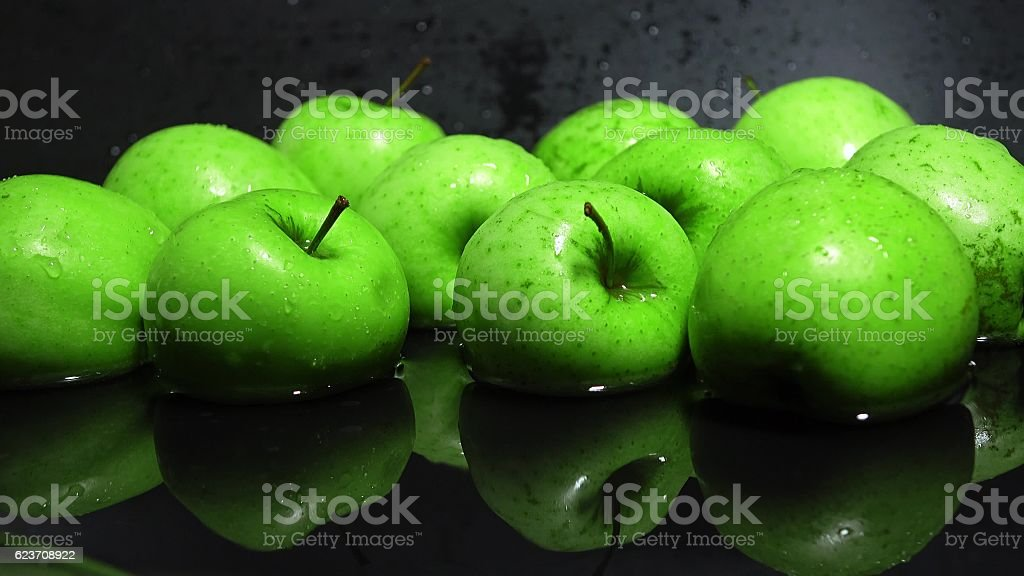 Green apples reflecting in water against black background stock photo
